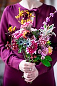 Woman holding bouquet in bright autumn colours