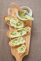 Bruschetta with avocado spread on chopping board (overhead)