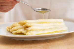 Butter being drizzled over white asparagus