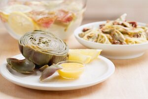 A cooked artichoke with vinaigrette
