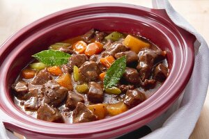 Beef stew being made in a slow cooker