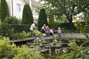 Frauen und kinder beobachten wassertiere am teich for Wassertiere teich
