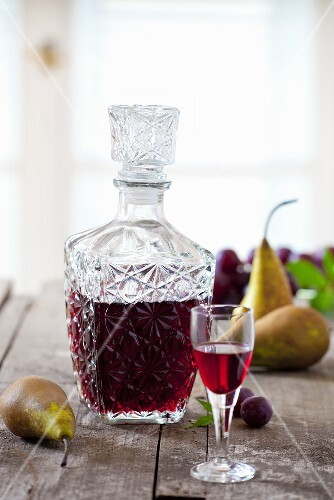 Homemade plum and pear liqueur in a glass and a carafe