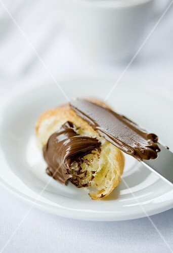 Chocolate spread on a croissant with a knife