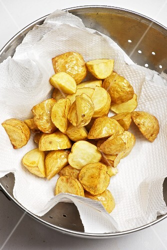 Deep fried potatoes being dried on kitchen paper