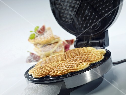 A waffle iron and a freshly baked waffle