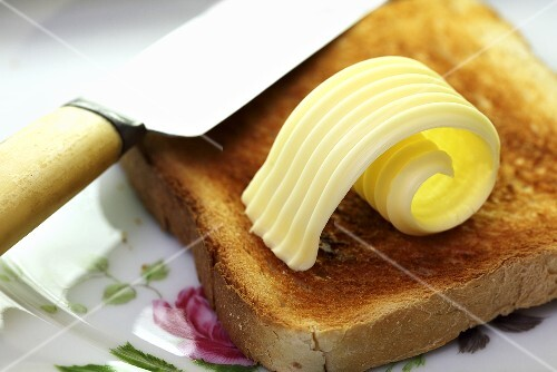 A slice of toast with a curl of butter