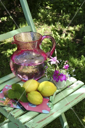 Lemons and a jug of water on a garden chair