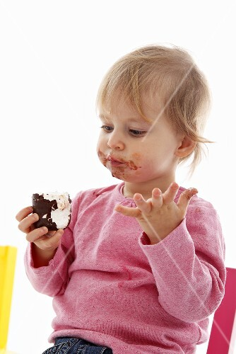 A small child eating a chocolate marshmallow