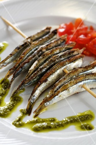 Grilled sardines on a skewer with pesto and tomato salad
