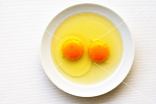 Two cracked eggs on a plate (seen from above)