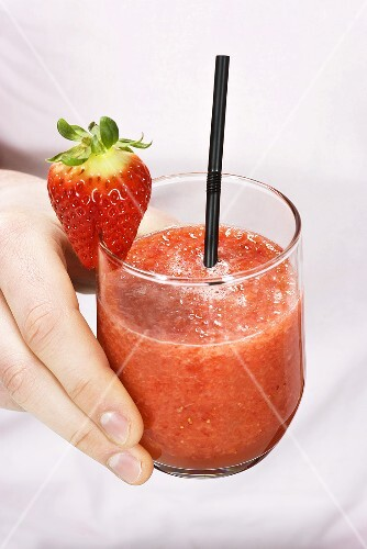 A hand holding a glass of strawberry smoothie