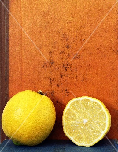 Whole lemon and half a lemon in front of a book