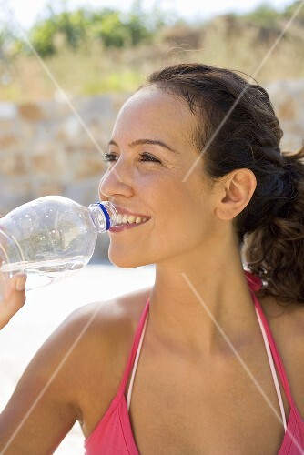 Woman drinking a bottle of mineral water