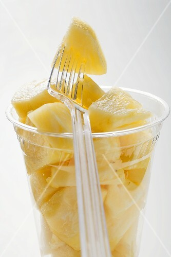 Pineapple chunks in a plastic beaker with a plastic fork