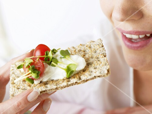 Woman eating crispbread with soft cheese, cress and tomato