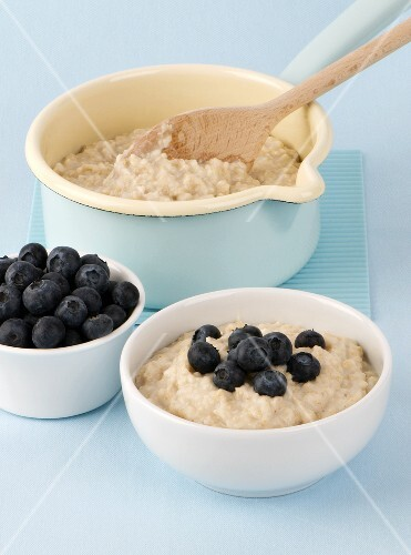 Porridge in a pan and in a bowl with blueberries