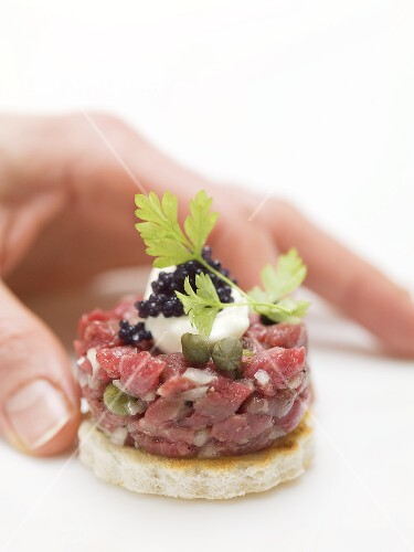 Hand reaching for tuna tartare canap stockfood for Canape dictionary