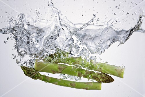 Green asparagus falling into water