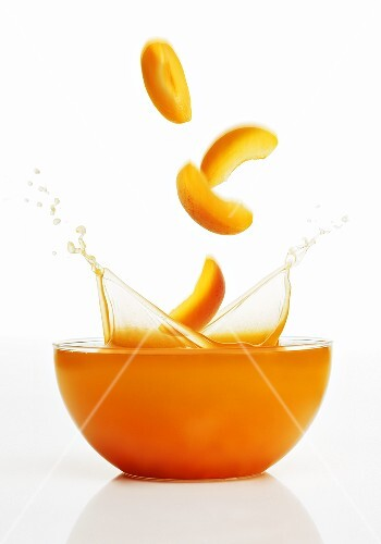 Apricot slices falling into apricot juice