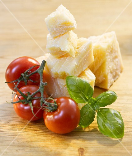 Tomatoes, basil and Parmesan on a wooden surface