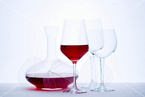 Glass of red wine, carafe and empty wine glasses