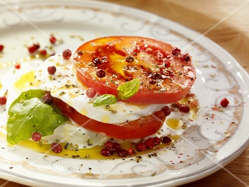 Tomatoes with mozzarella, basil, olive oil and pink peppercorns