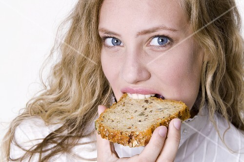 Young woman bitung into a slice of grannary bread
