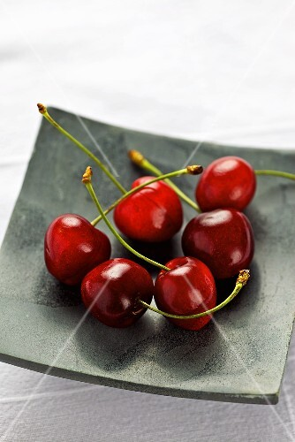 Several cherries on a square plate