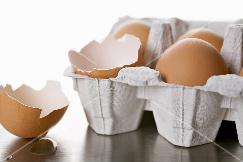 Eggs in egg box, one empty eggshell