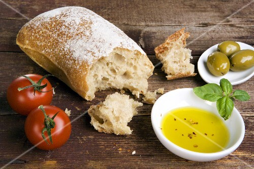 Still life with ciabatta, olive oil, olives and tomatoes