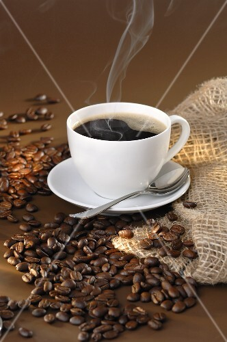 Steaming black coffee and coffee beans