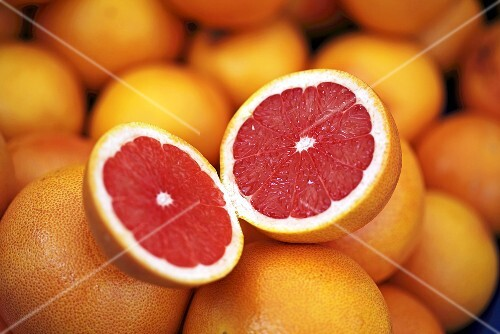 Pink grapefruits, one halved