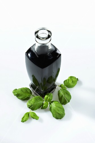 A bottle of balsamic vinegar and fresh basil