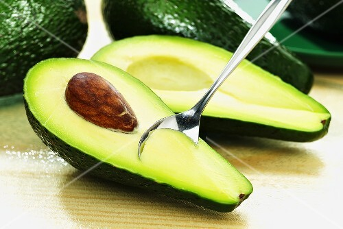 An avocado, halved, with a spoon