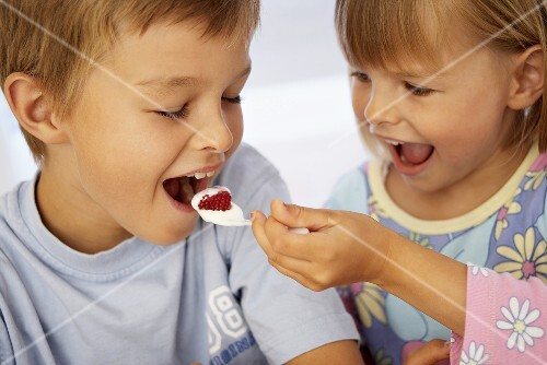 Girl putting a spoonful of yoghurt into a boy's mouth