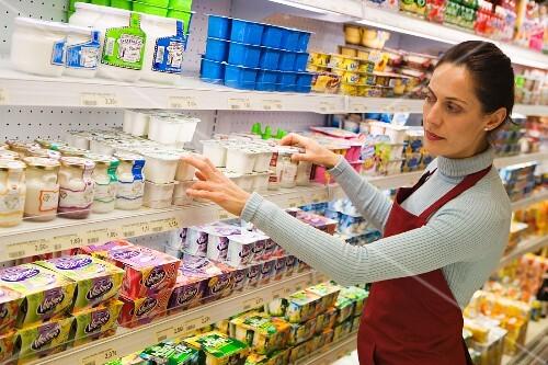 frau beim Regale einräumen im Supermarkt - Bild kaufen