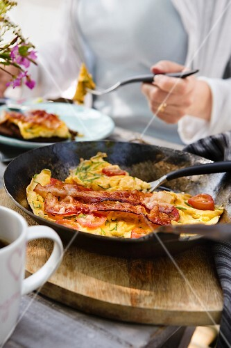 Omelette with bacon and tomatoes in a pan on a table