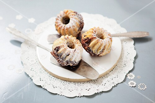 Mini marble Bundt cakes with icing sugar on a plate with a cake slice
