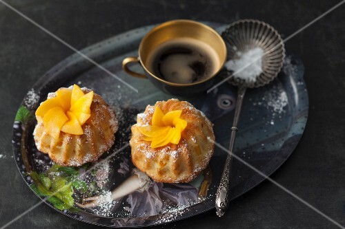 Mini mango and coconut Bundt cakes, a cup of coffee and a silver spoon