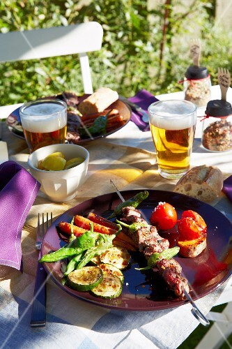 A skewer and grilled vegetables on a table in a garden