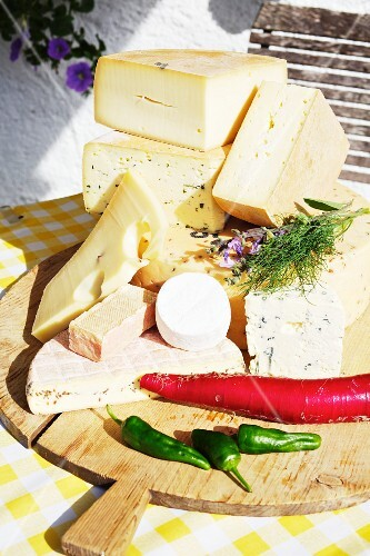 Various types of cheese on a wooden board