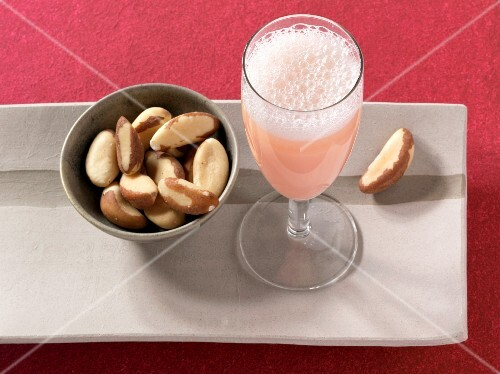 A bellini next to a dish of Brazil nuts