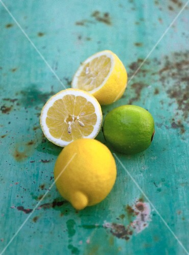 Limes and lemons, whole and halved, on a table