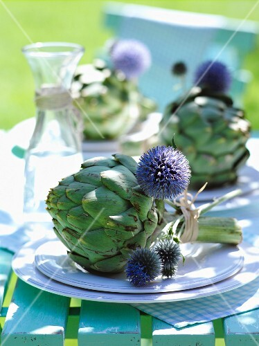 Artichokes tied together with thistle flowers as place setting decorations