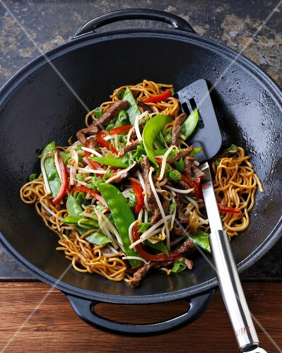 Stir-fried beef with noodles, mange tout and peppers