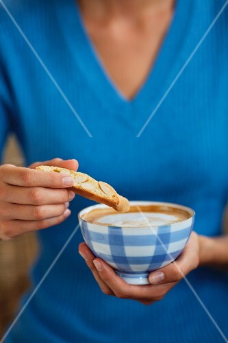 A woman dipping a biscuit into a cup of coffee