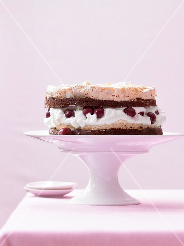A meringue cake filled with marinated cherries and cream on a cake stand