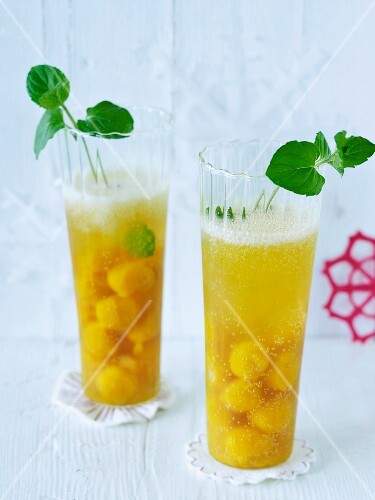 Two glasses of champagne with fruit puree balls and peppermint leaves