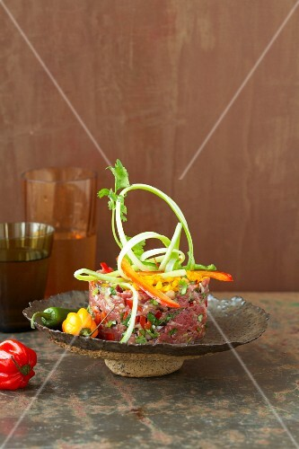 Raw marinated beef with strips of peppers and coriander